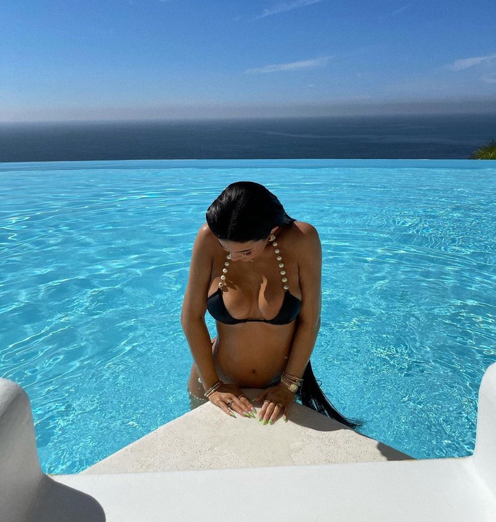 Bikini-clad, Kylie Jenner cups her ample cleavage as she poses inside a pool (Photos)