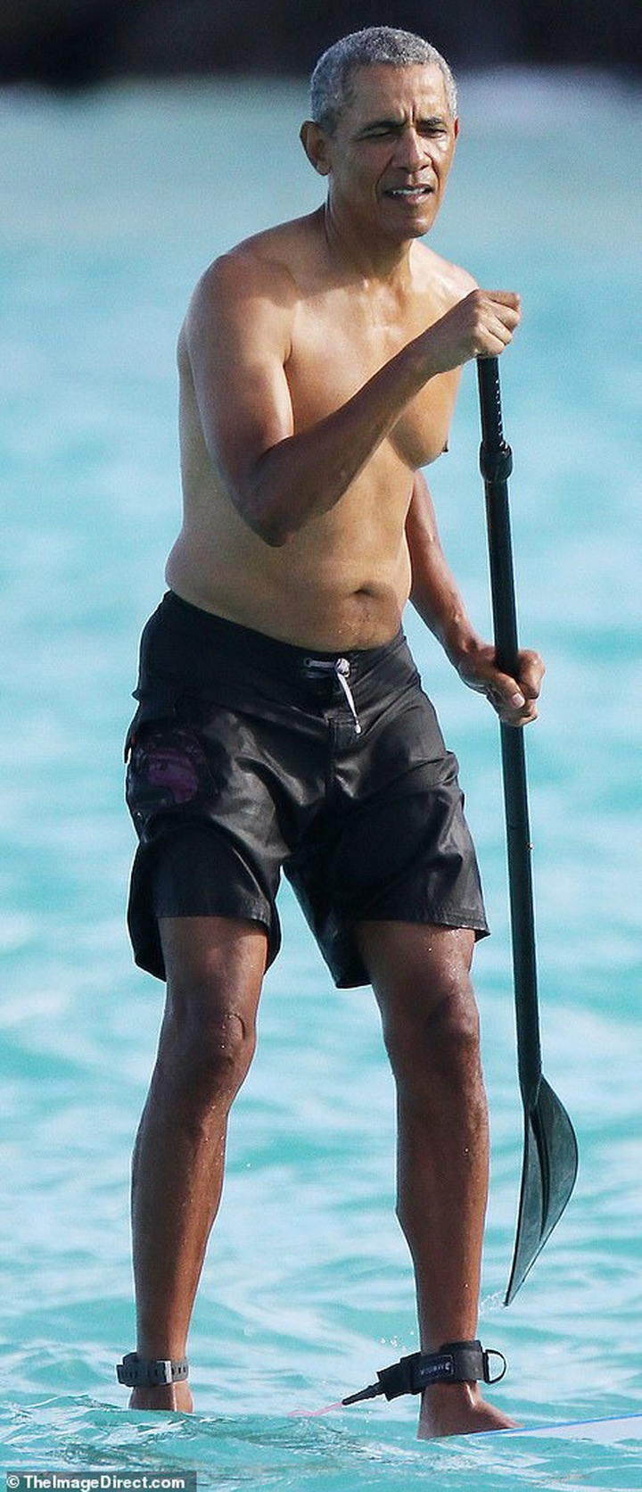 Shirtless Barack Obama shows off his fit physique during a paddle board session while on vacation in Hawaii (Photos)