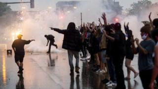 Police fired tear gas and protesters threw rocks and sprayed graffiti on police cars over George Floyd death