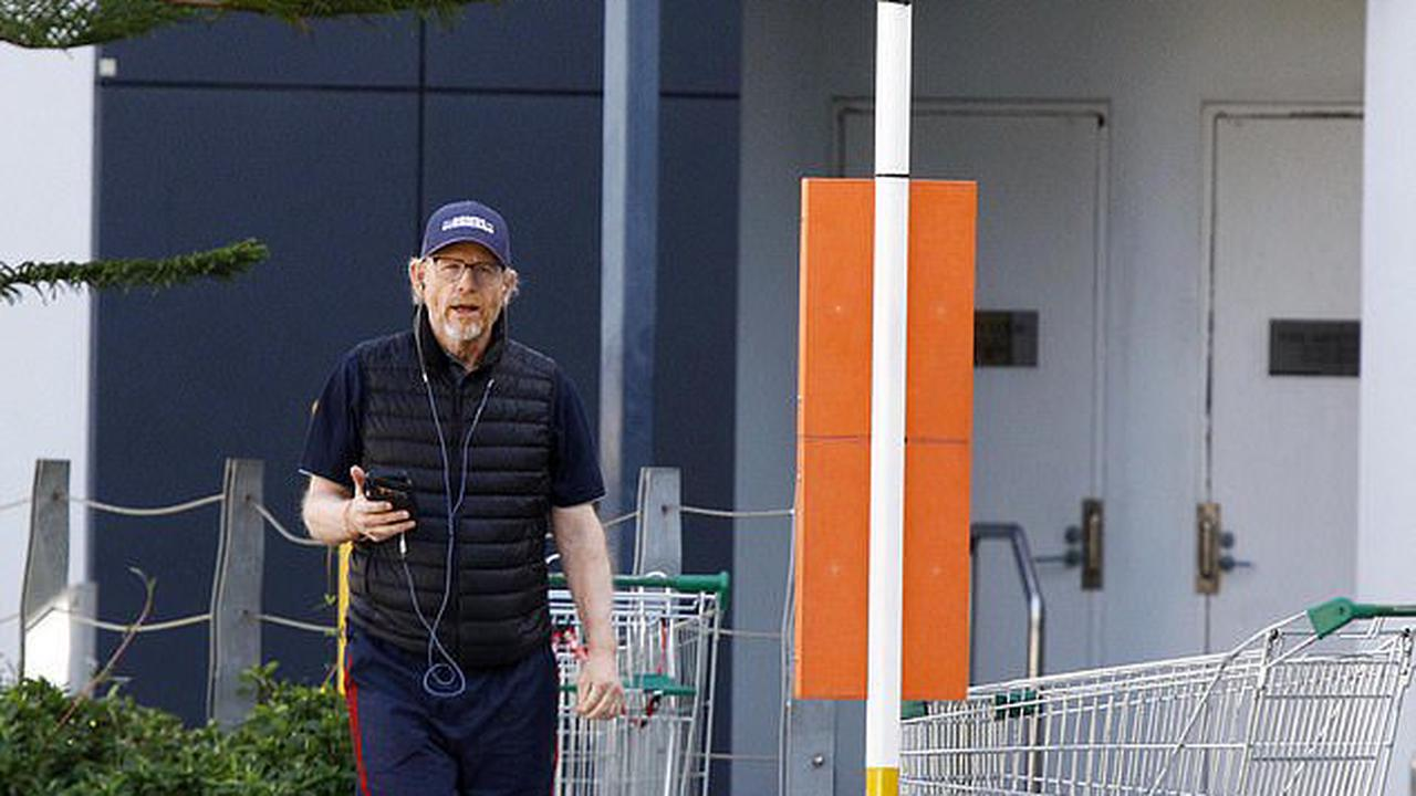 Just like the rest of us! Hollywood director Ron Howard waits by a local bus stop on the Gold Coast before eventually giving up and getting into an Uber