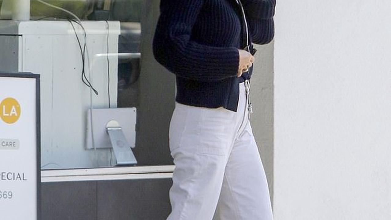 Gwyneth Paltrow looks summery in white slacks as she chats on the phone while shopping in Santa Monica... after skipping the line at the DMV