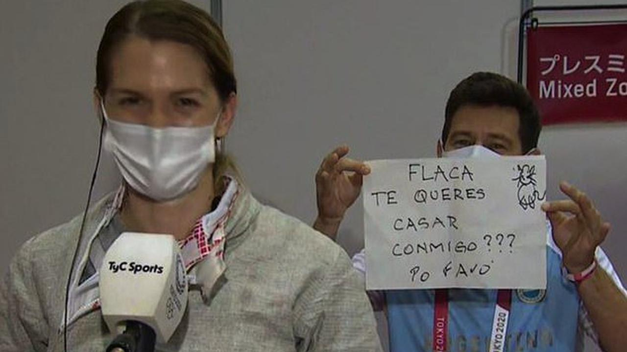 Argentina fencer gets ENGAGED after elimination from Tokyo Olympic Games as her coach pops the question with a handwritten sign during a TV interview