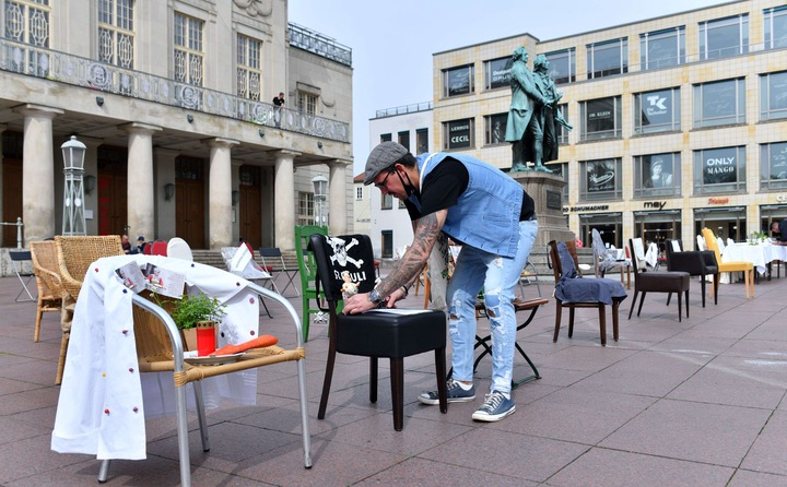 Slide 3 of 50: 24 April 2020, Thuringia, Weimar: Sven Schmidt, owner of a Weimar restaurant, places a chair from his restaurant on the Theaterplatz in front of the Goethe-Schiller monument. In several German cities, restaurateurs want to draw attention to their situation in the Corona crisis with empty chairs throughout the day. They hope that their restaurants and bars will open soon. Photo: Martin Schutt/dpa-Zentralbild/dpa (Photo by Martin Schutt/picture alliance via Getty Images)
