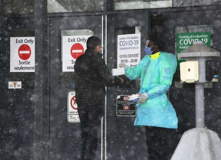 a person holding a sign: An Ottawa Public Health officer hands out protective gear to a person in line at a COVID-19 testing center in March 2020