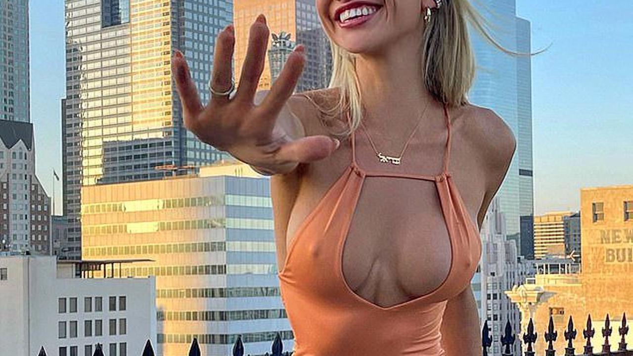 Would you wear this dress? Australian model risks a wardrobe malfunction as she poses in a VERY racy orange frock