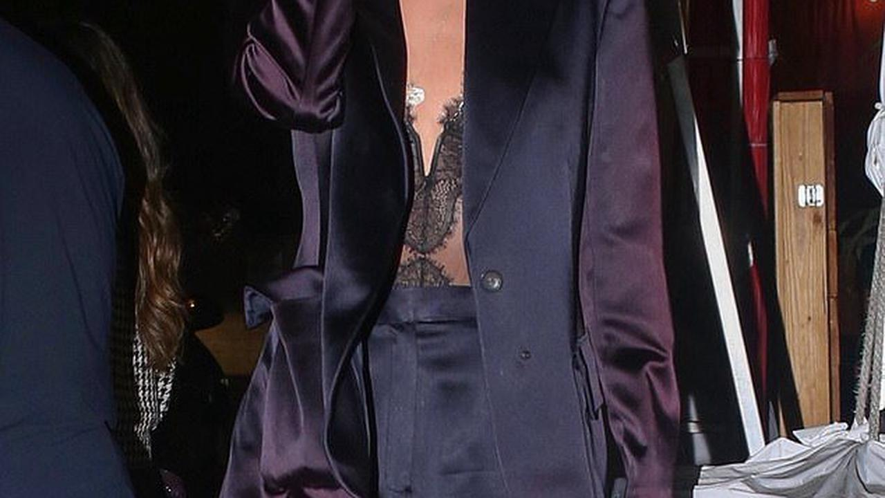 Stella Maxwell cuts a chic figure in a purple suit and low-cut lace top as she heads to dinner with friends
