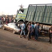 PHOTOS: Vehicle owner escapes death as truck loses control, climbs over his car in Lagos