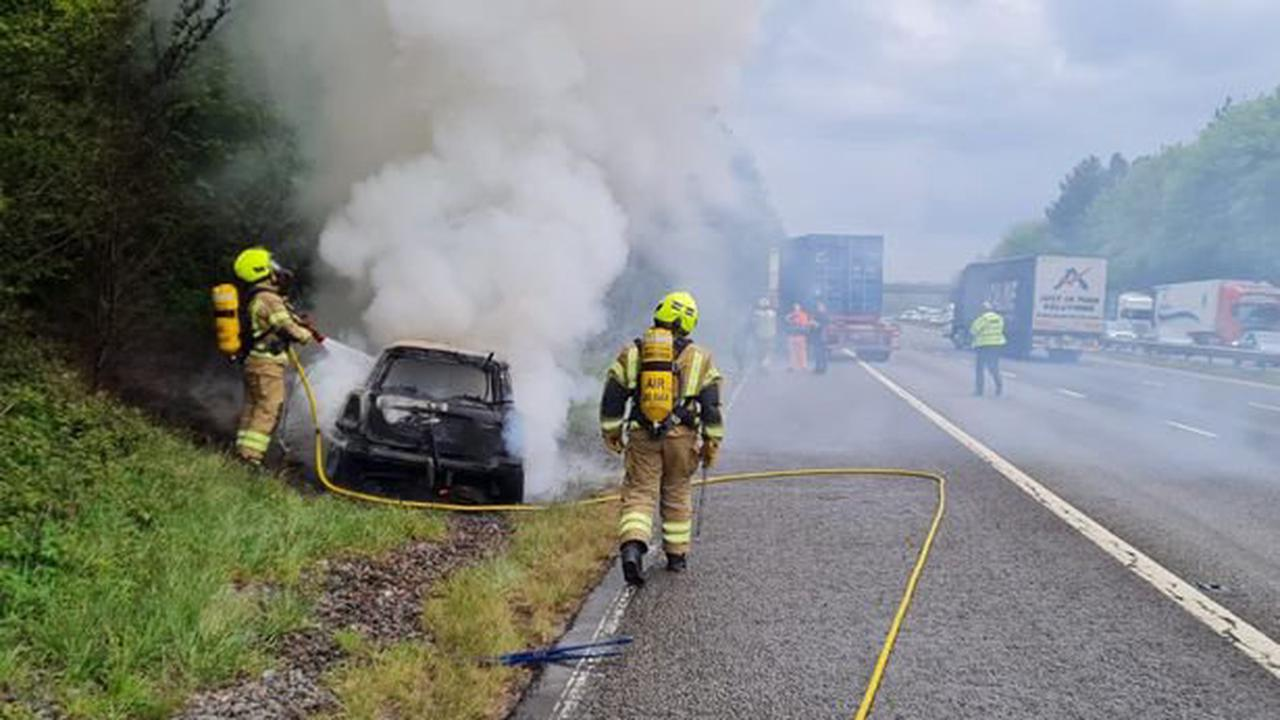 Smoke pours from charred remains of Mini which caught fire on the M1