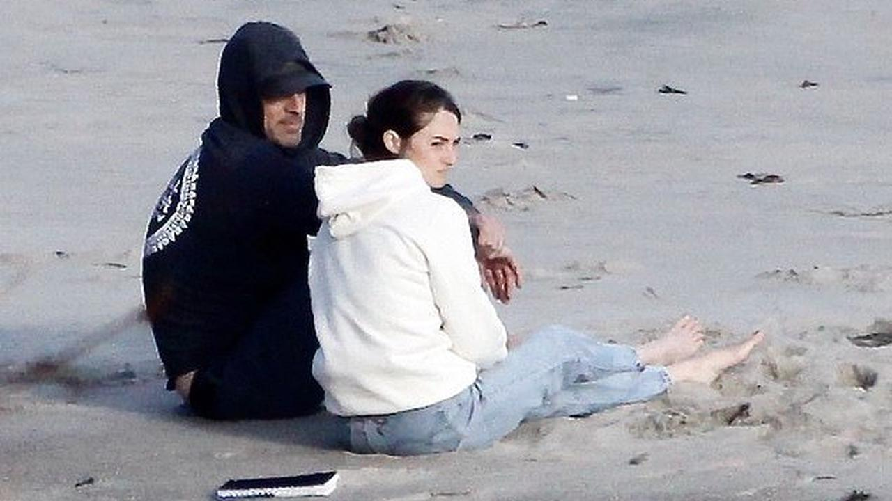 Shailene Woodley curls up on the beach with fiance Aaron Rodgers for relaxing evening watching the sunset alongside her furry friend