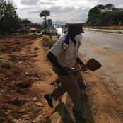 Traffic officer was seen filling in potholes after the heavy rains