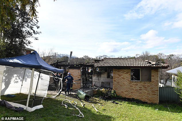 Fire investigators and forensic services at the scene of a house fire, where three year old twins died in the town of Batlow
