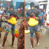 Un pousseur de brouette et son bébé au dos au marché d'Abobo