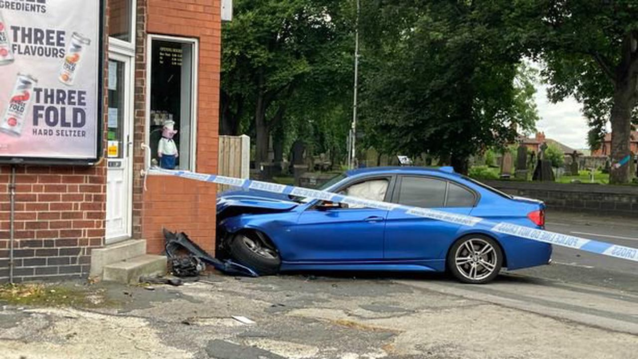 Police seal off Leeds road as BMW smashes into butchers after 2-car crash