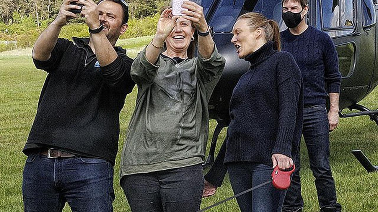 Tom Cruise poses for a socially-distanced selfie with fans as he lands via helicopter forMission: Impossible 7 filming in the outskirts of London