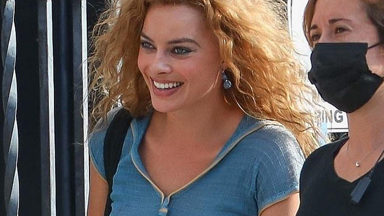 Margot Robbie conceals her signature blonde hair beneath a wavy auburn wig as she shoots scenes for upcoming film Babylon in Los Angeles