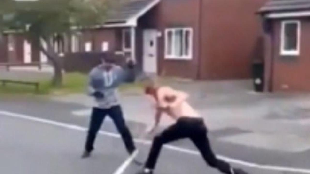 Horrific moment two bloodied men attack each other with machetes in front of shocked families on a residential street in Lancashire