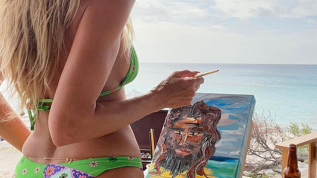 Heidi Klum shares a VERY cheeky bikini photo while seemingly painting a portrait of husband Tom Kaulitz during beach day