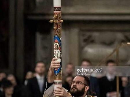 What does the big candle Catholics use at easter vigil represents