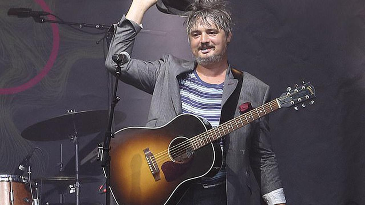 Pete Doherty tips his flat cap after performing at the Make Music Day concert in Paris... following move to France and embracing clean-living