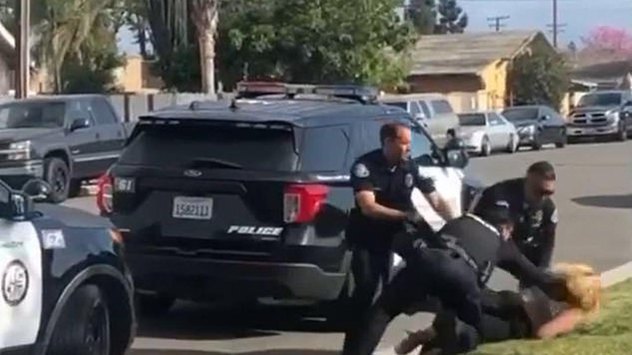 California cop is RESTRAINED by his own colleagues after repeatedly punching handcuffed woman in the head during arrest