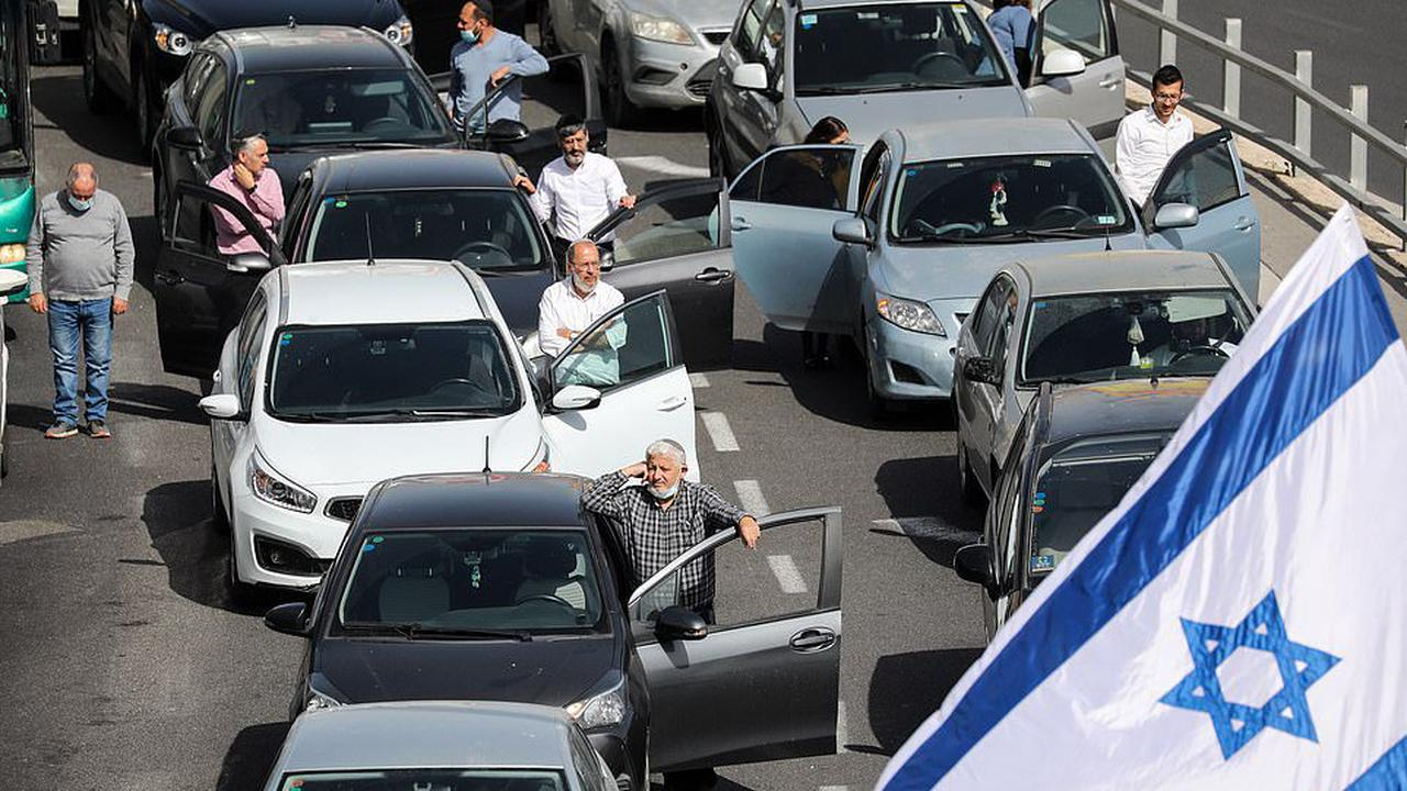 Israel falls silent to remember the horrors of the Holocaust: Traffic comes to a halt and families stand with heads bowed across the state to mark WWII's six million Jewish victims