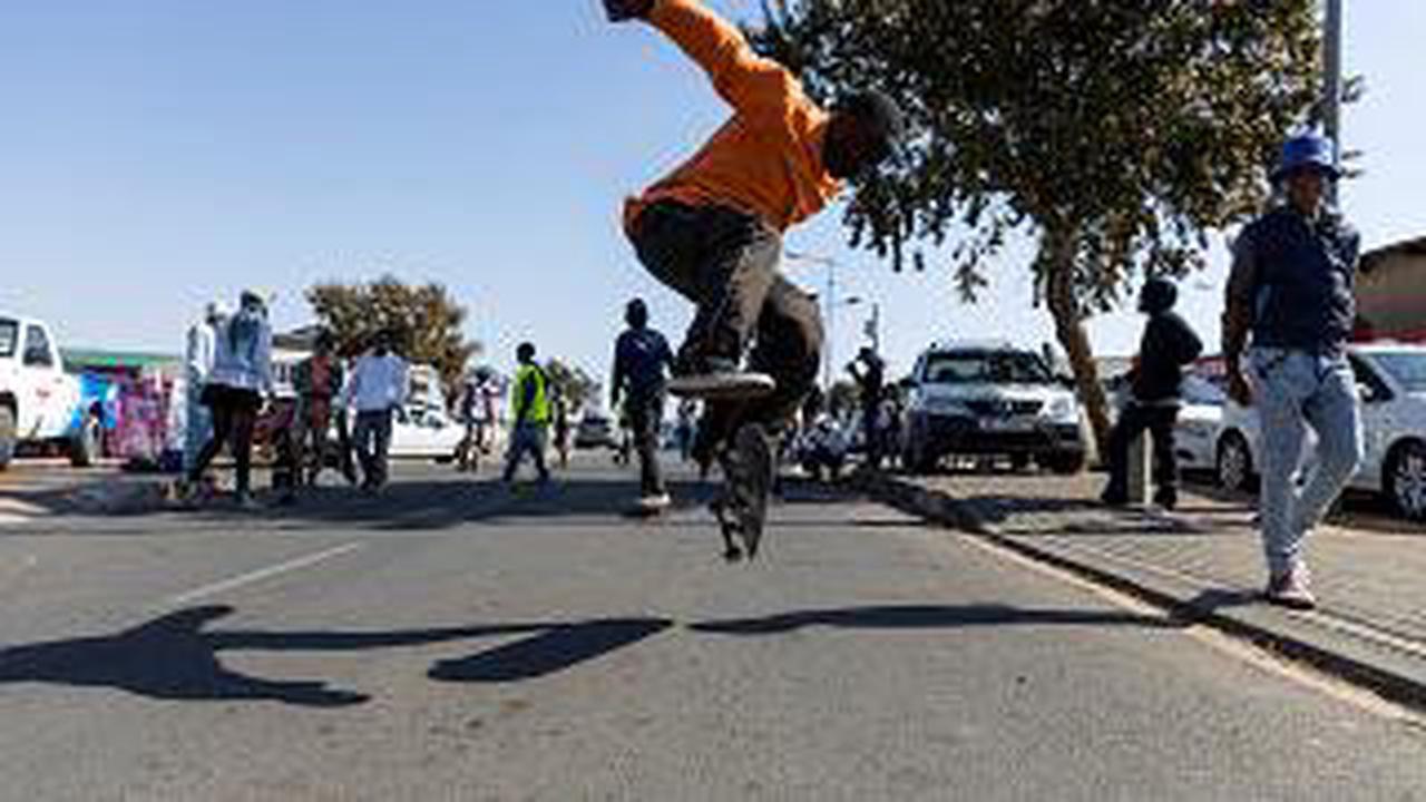 Soweto-Skateboarder surfen die Straße hinunter