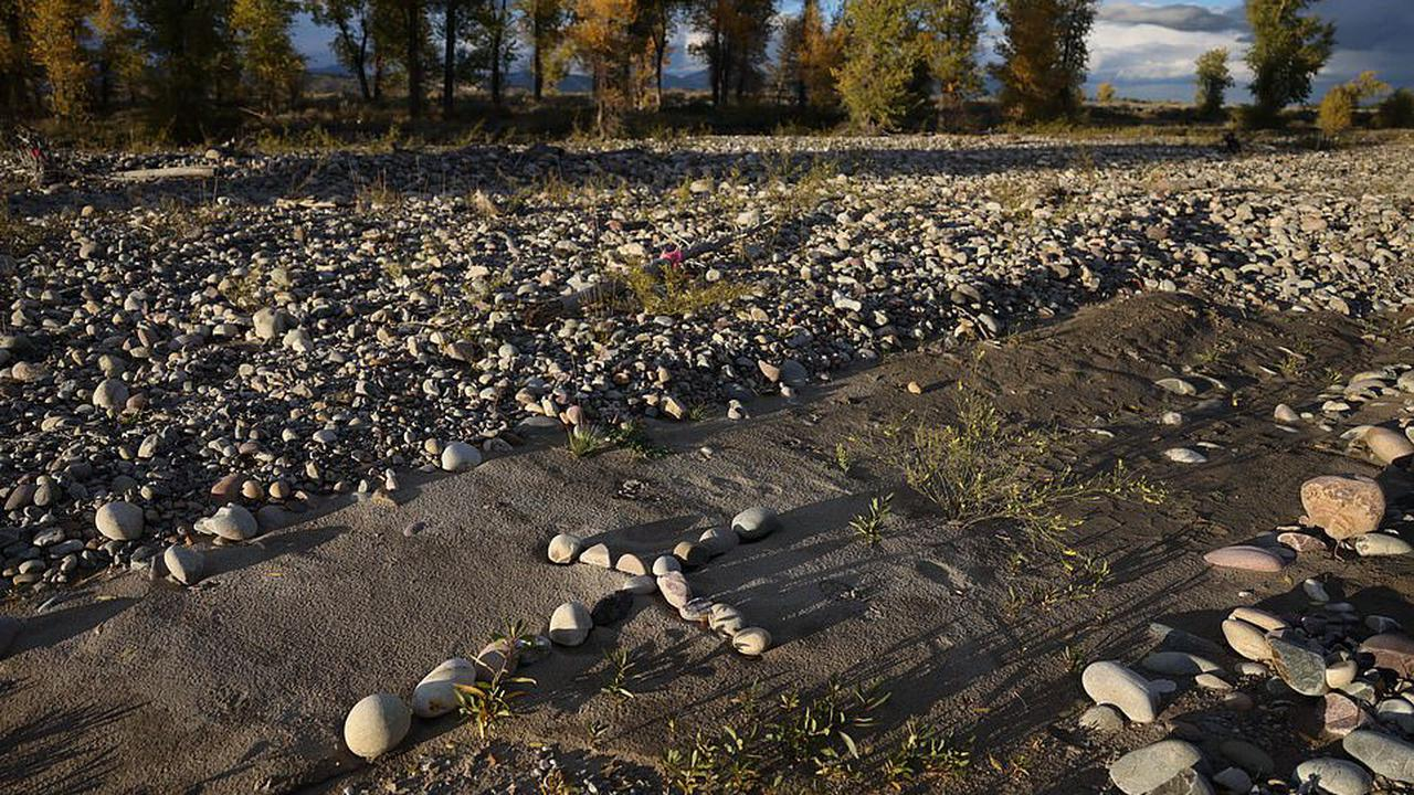 EXCLUSIVE: Stones arranged in a cross are left as an apparent memorial at Wyoming campsite where body believed to be 22-year-old 'van life' woman Gabby Petito was found