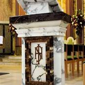 What is the symbolism and importance of an ambo in the Catholic Church?