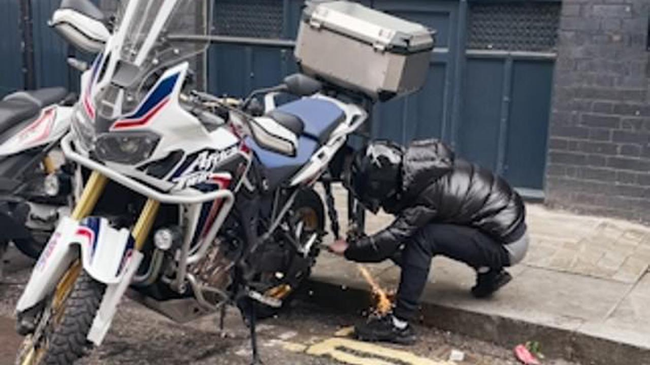 EXCLUSIVE: Moment cyclist confronts angle grinder-wielding motorbike thieves in broad daylight - before pushing one over as they try to flee on the £13,000 vehicle